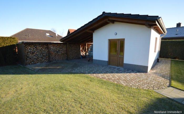 Gerätehaus mit Überdachung und Holzlager