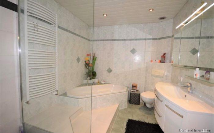 Badezimmer mit Dusche, Wanne und Handtuchtrockner