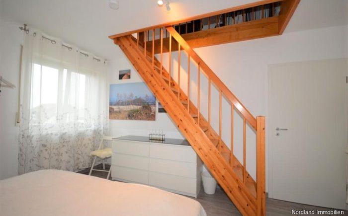 Schlafzimmer mit Treppe zum ausgebauten Dachboden