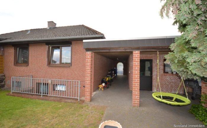 Gartenansicht / Wohnhaus mit Kelleraußentreppe, Garage und überdachter Durchgang zum Vorgarten