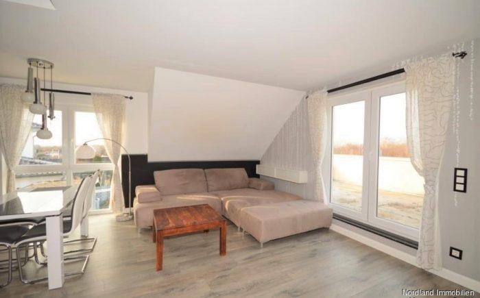 Wohnzimmer mit Zugang zum großzügigen Balkon